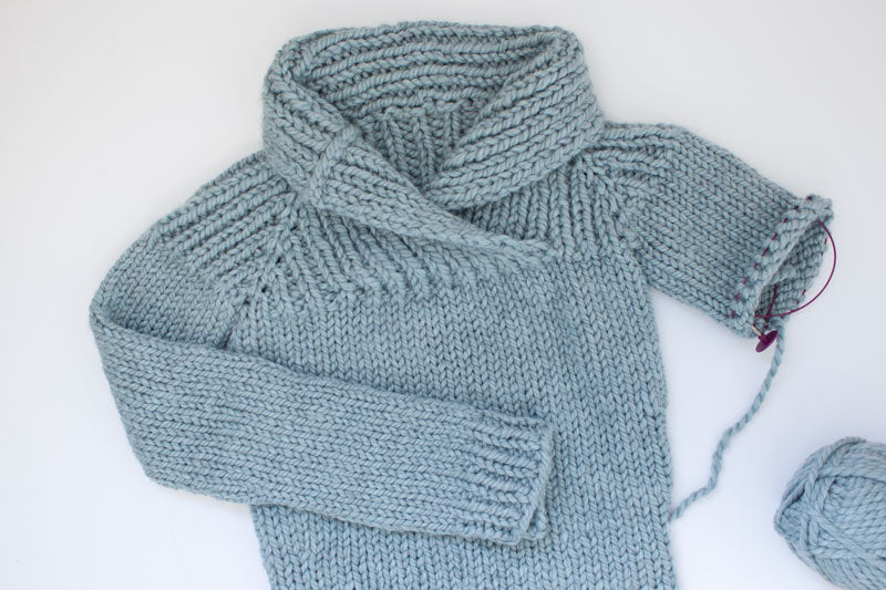 flat lay of an unfinished bulky hand knit sweater with shawl collar in grey blue