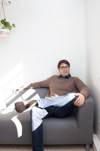 man on couch with crossed leg wearing blue jeans and handknit brown pullover