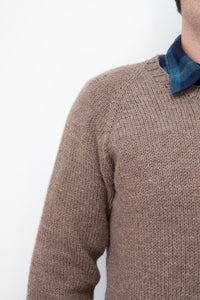 close up of raglan increases on hand knit sweater worn by a man in a flannel blue collared shirt