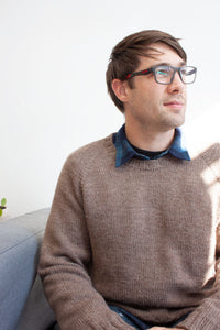 man sitting on grey couch wearing glasses and blue jeans modeling handknit raglan pullover