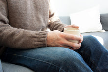 Load image into Gallery viewer, close up of mans hands holding a white coffee cup, he is wearing blue jeans and handknit brown pullover