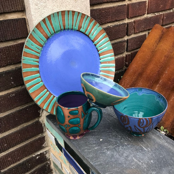 Collection of handmade ceramics by Liz Kinder. Large serving plate, deep bowls, and mug. All deep blue and green with gold accents.