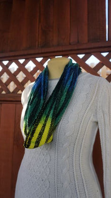 Hand dyed black, yellow, green and blue handwoven scarf made in Bend Oregon wrapped around and paired with a white sweater