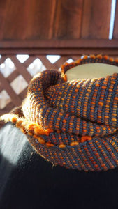 Hand dyed orange wool and grey bamboo handwoven scarf made in Bend Oregon wrapped around and paired with a black sweater