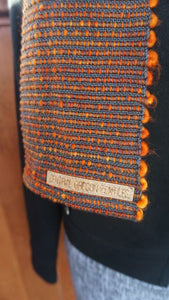 Hand dyed orange wool and grey bamboo handwoven scarf made in Bend Oregon wrapped around and paired with a black sweater close-up