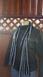 Black and white stripes handwoven scarf made in Bend Oregon wrapped around the neck and paired with an olive green jacket