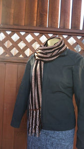 Black and copper stripes handwoven scarf made in Bend Oregon wrapped around and paired with a olive green sweater