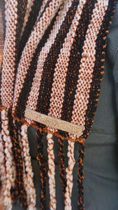 Black and copper stripes handwoven scarf with tassels made in Bend Oregon wrapped around and paired with a olive green sweater