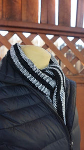 Black and white stripes handwoven scarf made in Bend Oregon wrapped around the neck and paired with a black vest