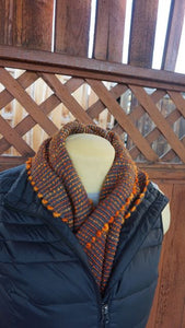 Hand dyed orange wool and grey bamboo handwoven scarf made in Bend Oregon wrapped around and paired with a black vest