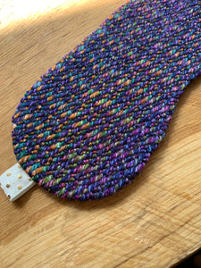 Handwoven eye mask made from purple wool and black bamboo with white and gold elastic band