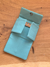 Load image into Gallery viewer, Handwoven teal, white, and blue handwoven cotton fabric sewn with wool and cork to organize your earrings and necklaces during travel.