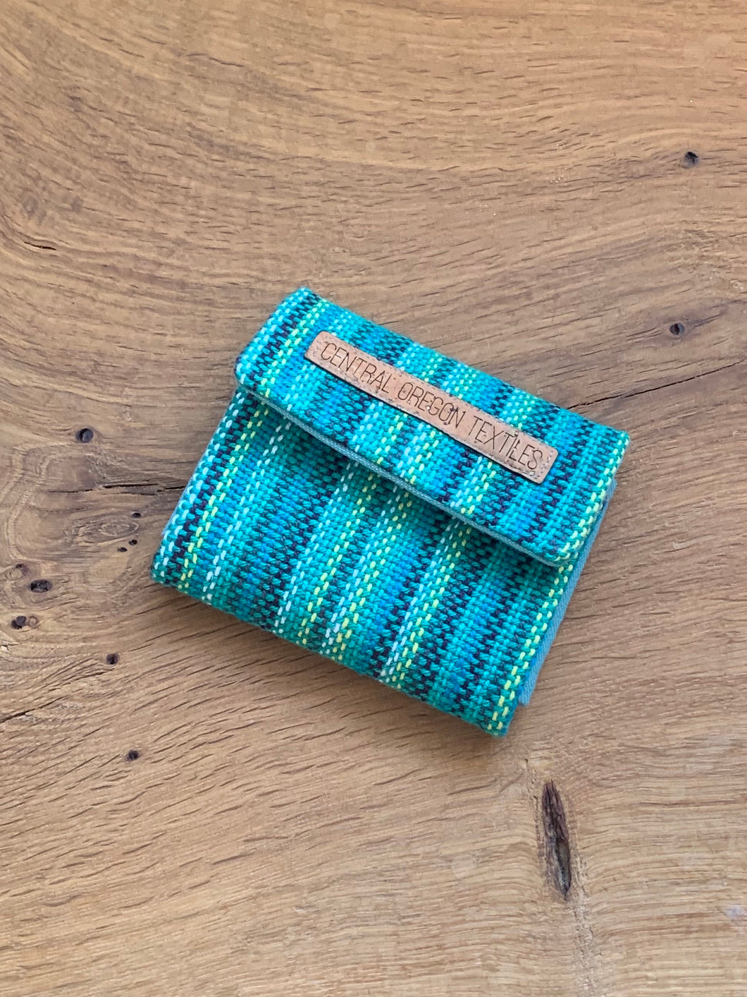 Handwoven teal, white, and blue handwoven cotton fabric sewn with wool and cork to organize your earrings and necklaces during travel.
