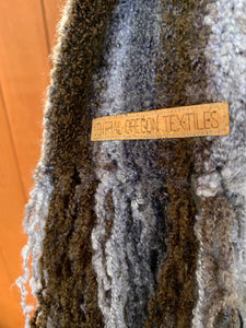 Close up of the brown and grey striped handwoven scarf with a cork label