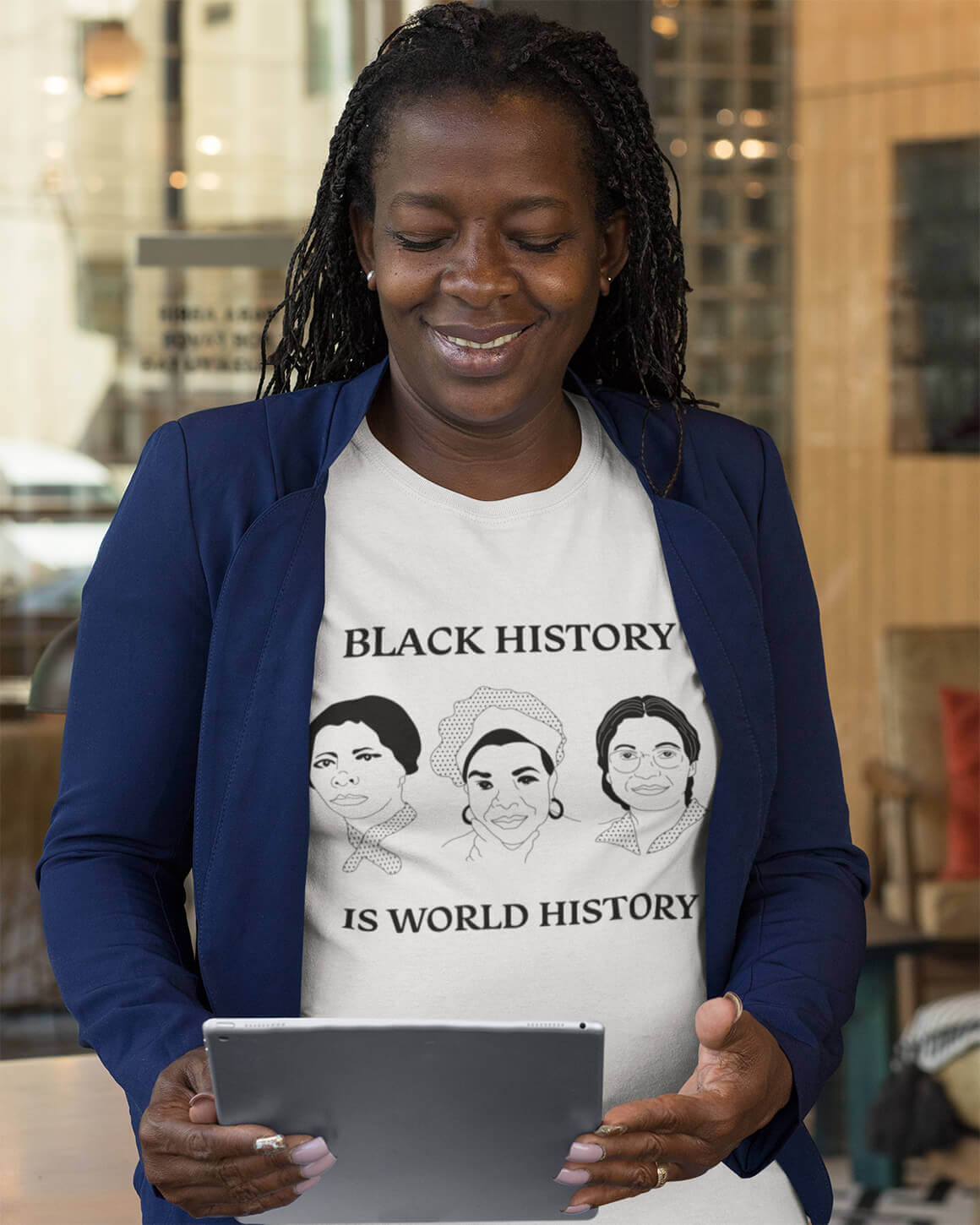 Professional woman in feminist t-shirt depicting Maya Angelou, Harriet Tubman, and Rosa Parks