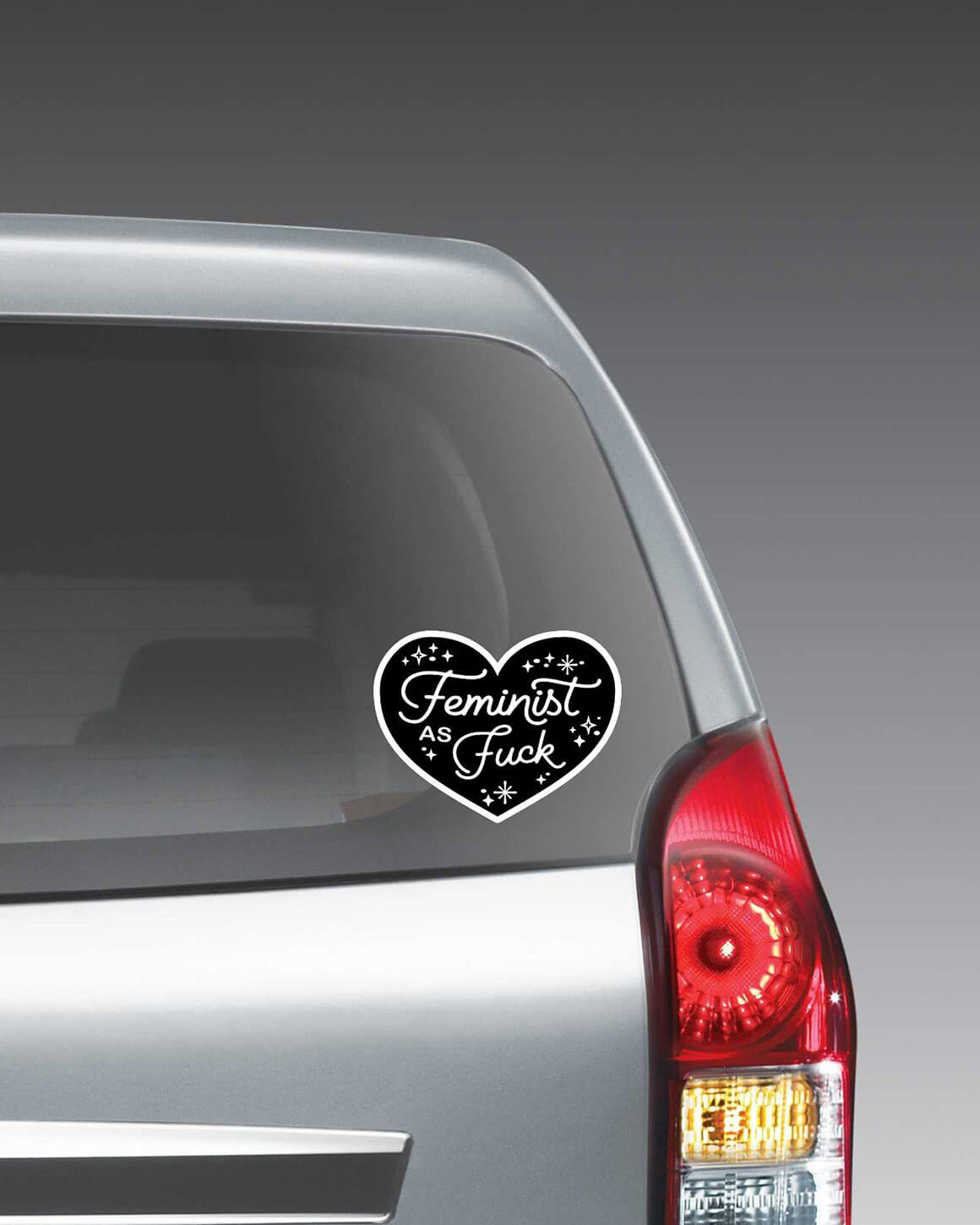 Black feminist car decal in a heart shape with the phrase Feminist as Fuck