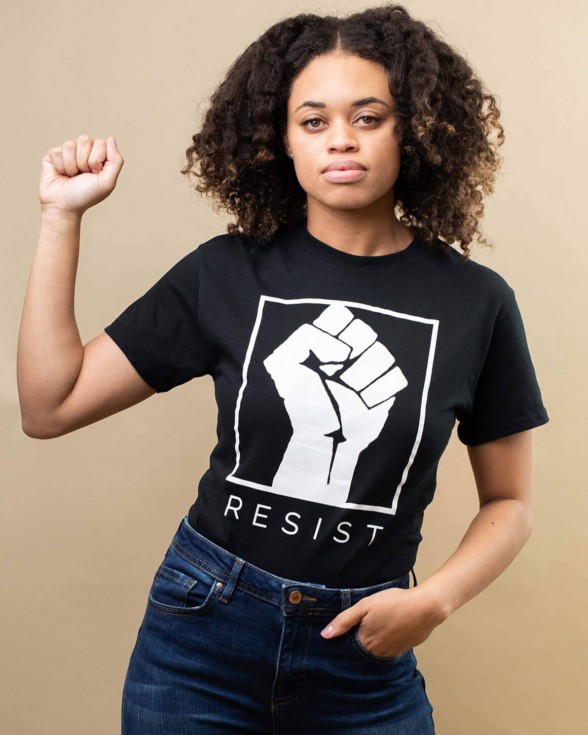 Young woman looking into the distance wearing black feminist fist t shirt