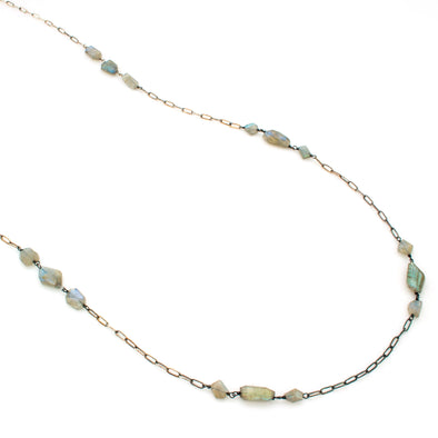 A One-of-a-Kind Necklace featuring Natural Labradorite faceted gemstone beads, set in clusters along an oxidized Sterling silver Chain, handmade by Tribe Jewelry Designer Sarah Lewis.
