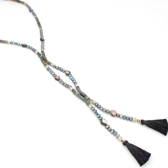A One-of-a-Kind Beaded Lariat Beaded Necklace featuring Labradorite, Magnetized Hematite, Pearls, and Black Silk Tassels, handmade by Tribe Jewelry Designer Sarah Lewis.