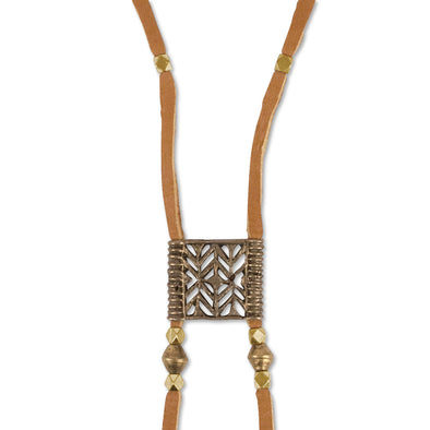 A Bohemian Bolo style necklace, featuring an antique bronze medallion, hanging on a long, brown leather cord, with brass beads, handmade by Tribe Jewelry Designer Sarah Lewis.