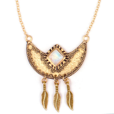 A Bohemian style Gold Plated Necklace featuring a Natural Moonstone set in a Crescent Moon Pendant, featuring granulation design, hammered texture and 3 hanging Silver feathers, by Tribe Jewelry Designer Sarah Lewis.