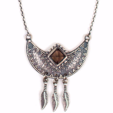 A Sterling Silver Necklace featuring a Pyramid cut Smokey Quartz Crystal set in a Crescent Moon Pendant, featuring granulation design and hammered texture with 3 hanging Silver feathers.