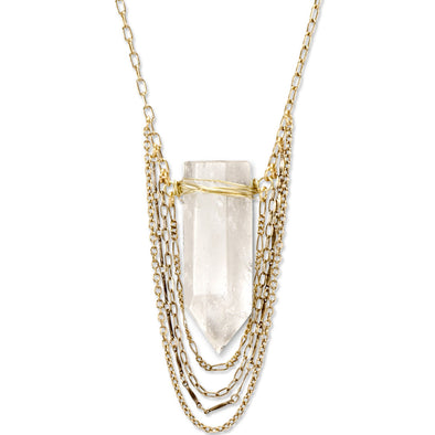 A Bohemian Statement Necklace, featuring a wire wrapped Quartz Crystal hanging from gold plated chains, handmade by Tribe Jewelry Designer Sarah Lewis.