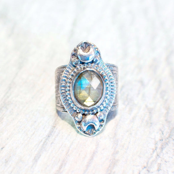 Iridescent, Rainbow Labradorite set in a Sterling Silver Ring. Stone is flanked by two fine silver crescent moons and stamped radial design. Band features geometric pattern.