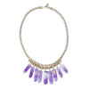 A Bohemian style Statement Bib Necklace featuring a Fringe of Amethyst Crystals, hanging from an antiqued, gold plated Chain, handmade by Tribe Jewelry Designer Sarah Lewis.