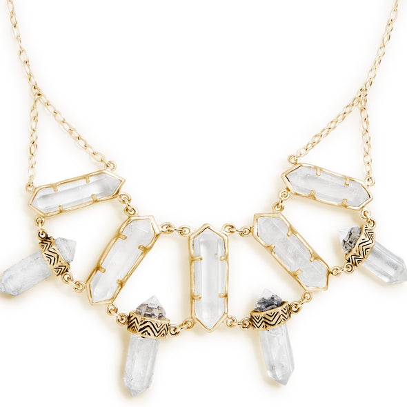 A Bohemian style, statement Bib Necklace, featuring 9 Quartz Crystals set in 18K Gold Plated Sterling Silver, handmade by Tribe Jewelry Designer Sarah Lewis.