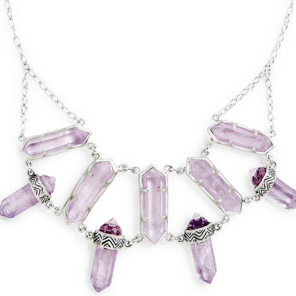 A Bohemian style, statement Bib Necklace, featuring 9 Amethyst Crystals set in Sterling Silver, handmade by Tribe Jewelry Designer Sarah Lewis.