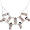 A Bohemian style, statement Bib Necklace, featuring 9 Smokey Quartz Crystals set in Sterling Silver, handmade by Tribe Jewelry Designer Sarah Lewis.
