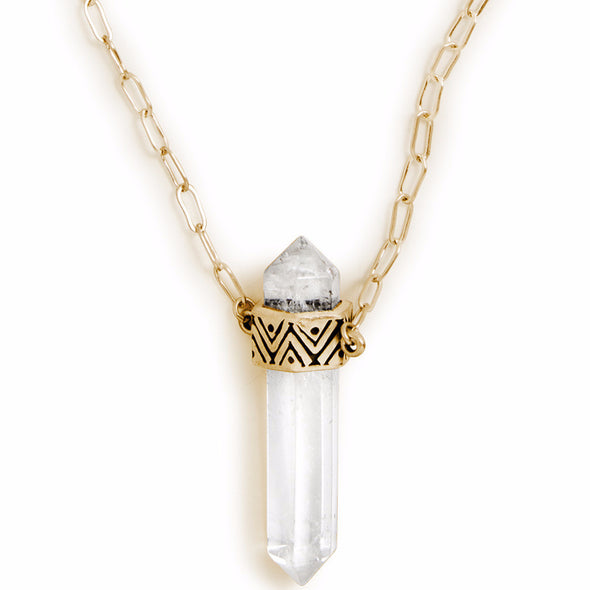 A Bohemian style Gold Plated, Quartz Crystal Pendant Necklace featuring a carved, geometric pattern on setting, handmade by Tribe Jewelry Designer Sarah Lewis.