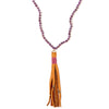 A Bohemian Mala style Necklace featuring a soft Suede Tassel, hanging from a strand of faceted Amethyst gemstone beads, handmade by Tribe Jewelry Designer Sarah Lewis.