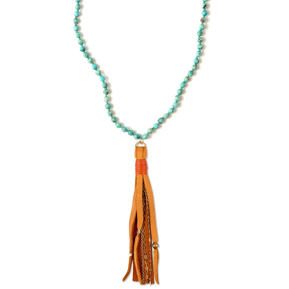 A Mala style Necklace featuring a soft Suede Tassel, hanging from a knotted strand of natural, faceted Turquoise gemstone beads, handmade by Tribe Jewelry Designer Sarah Lewis.