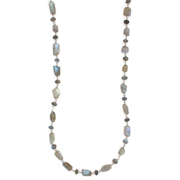 A Long Bohemian Beaded Necklace made of Faceted Labradorite gemstones on a wire-wrapped chain, paired with an artisanal Silver plated chain, handmade by Tribe Jewelry Designer Sarah Lewis.