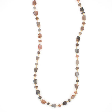 A Long Bohemian Beaded Necklace featuring Faceted Moonstone gemstones on a wire-wrapped chain, paired with an artisanal Gold plated chain, by Tribe Jewelry Designer Sarah Lewis.