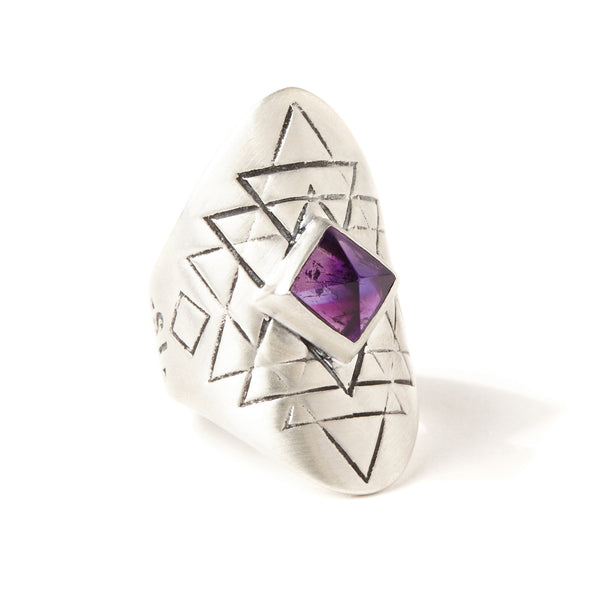 A bohemian style statement ring featuring an amethyst stone set in sterling silver, with carved geometric sri yantra design, by Tribe Jewelry Designer Sarah Lewis.
