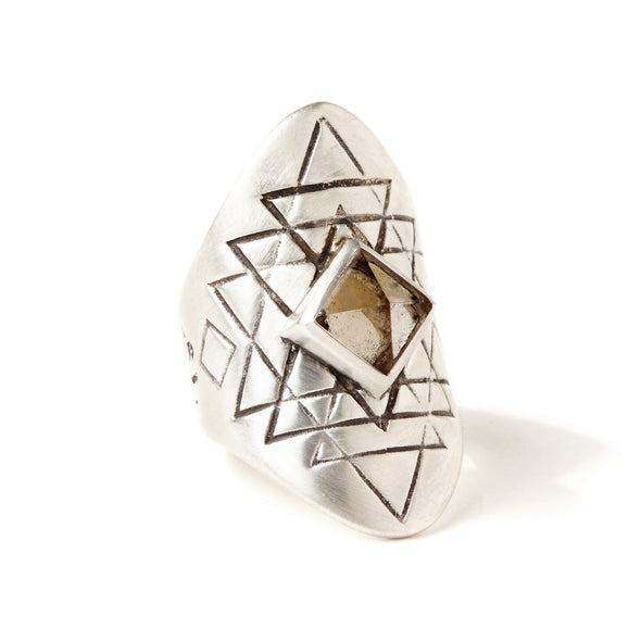 A bohemian style statement ring featuring a smokey quartz crystal pyramid set in sterling silver, with carved geometric sri yantra design, by Tribe Jewelry Designer Sarah Lewis.