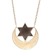 A Bohemian style Necklace features a bronze crescent moon and star medallion, hanging on an antiqued gold plated chain, handmade by Tribe Jewelry Designer Sarah Lewis.