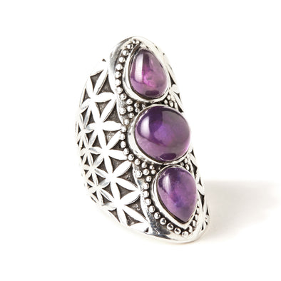 A Bohemian style statement ring featuring 3 Amethyst Cabochons set in oxidized Sterling Silver, with a carved Flower of Life pattern pattern around band, by Tribe Jewelry Designer Sarah Lewis.