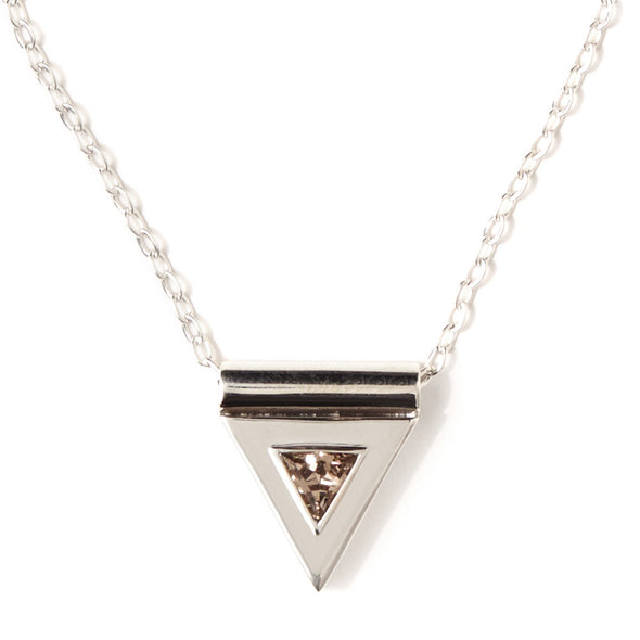 A sterling silver necklace, featuring a faceted, smokey quartz gemstone, in a triangular pendant, handmade by Tribe Jewelry Designer Sarah Lewis.