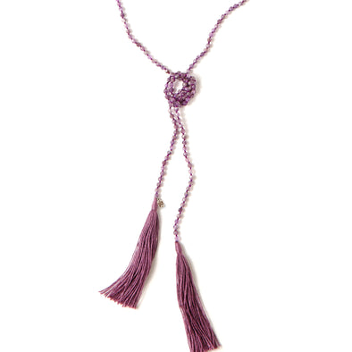A Bohemian style Lariat Necklace, featuring 2 cotton tassels hanging from a long strand of natural, faceted amethyst stone beads, by Tribe Jewelry Designer Sarah Lewis.