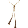 A Bohemian style Lariat Necklace, featuring 2 cotton tassels hanging from a long strand of natural, faceted labradorite stone beads, by Tribe Jewelry Designer Sarah Lewis.
