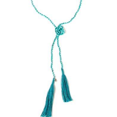 A Bohemian style Lariat Necklace, featuring 2 tassels hanging from a long strand of natural, faceted turquoise stone beads, by Tribe Jewelry Designer Sarah Lewis.
