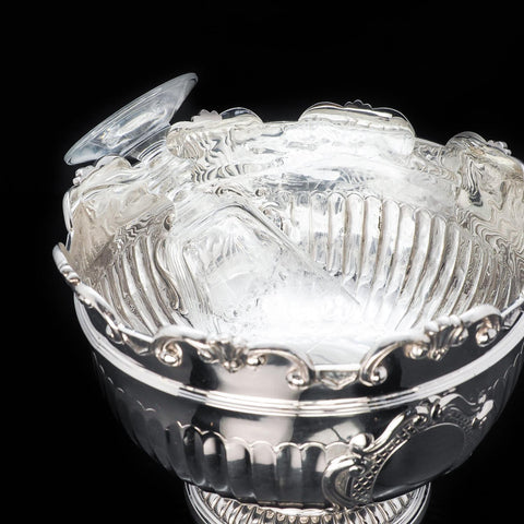 A glass hanging in a solid silver monteith bowl