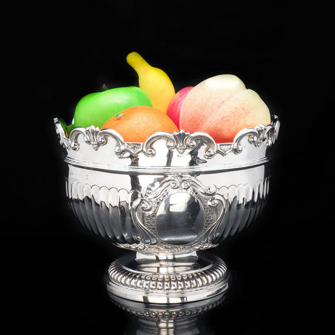 a silver monteith bowl with fruits inside