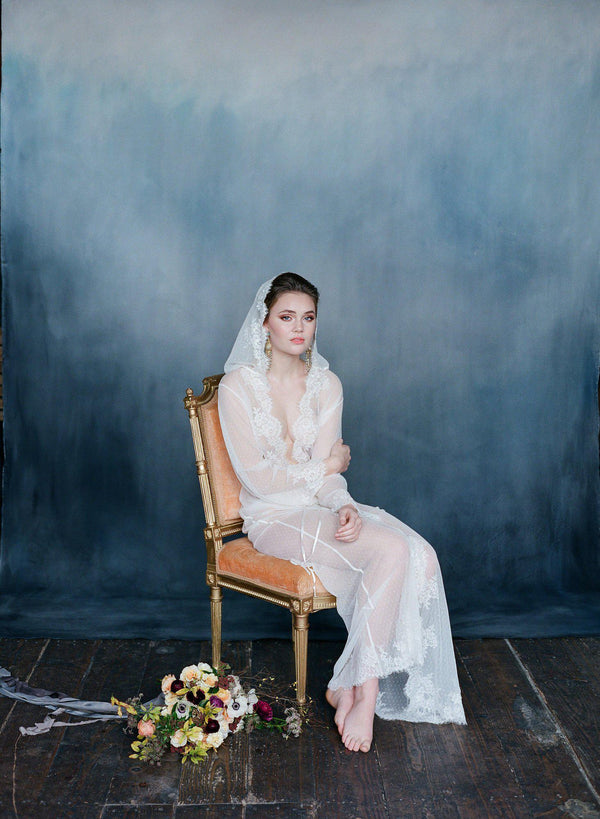 Bride sitting wearing ivory dotted lace robe with hood