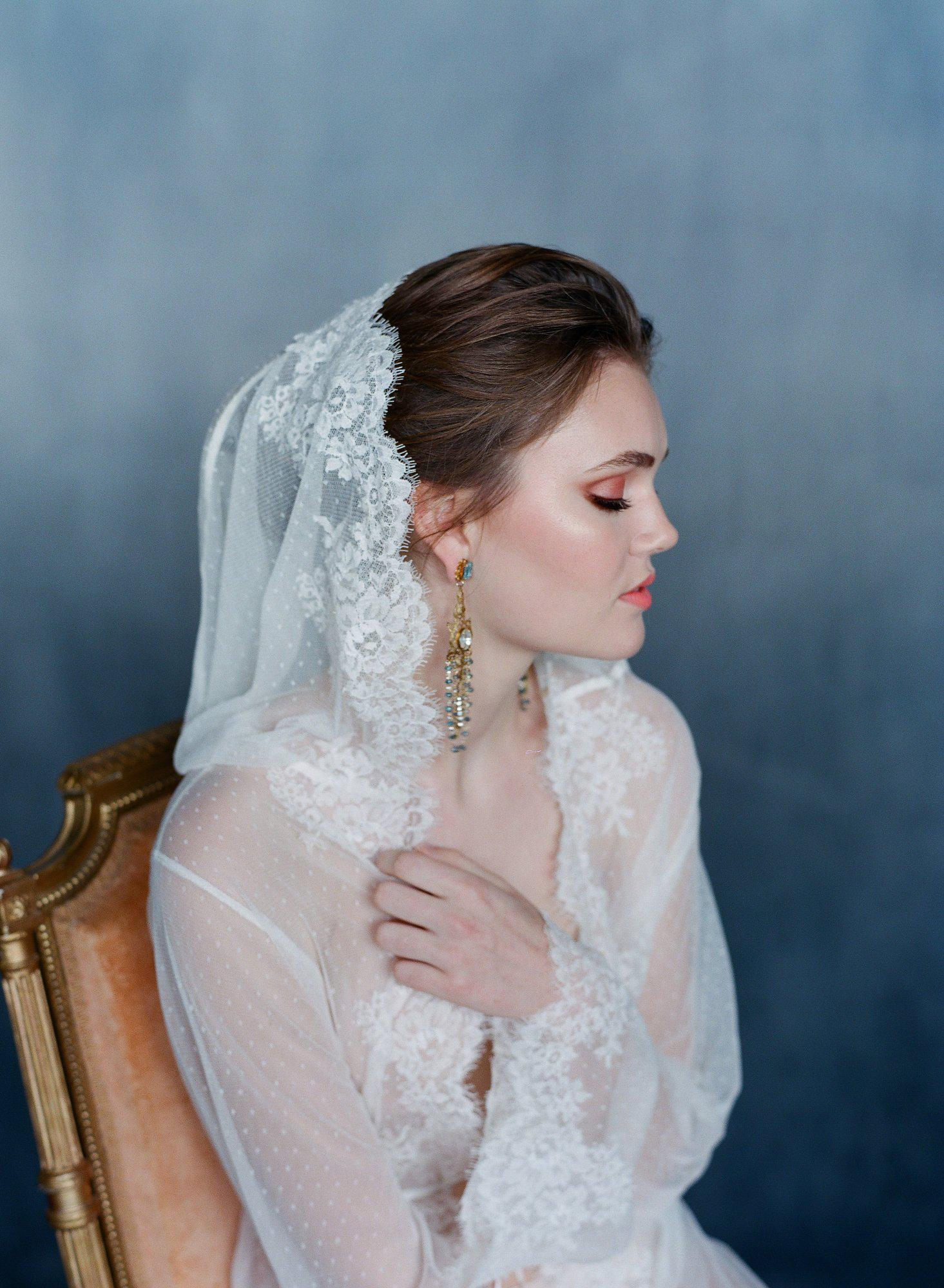 Bride showing a side view wearing a dotted lace robe with hood and lace trim