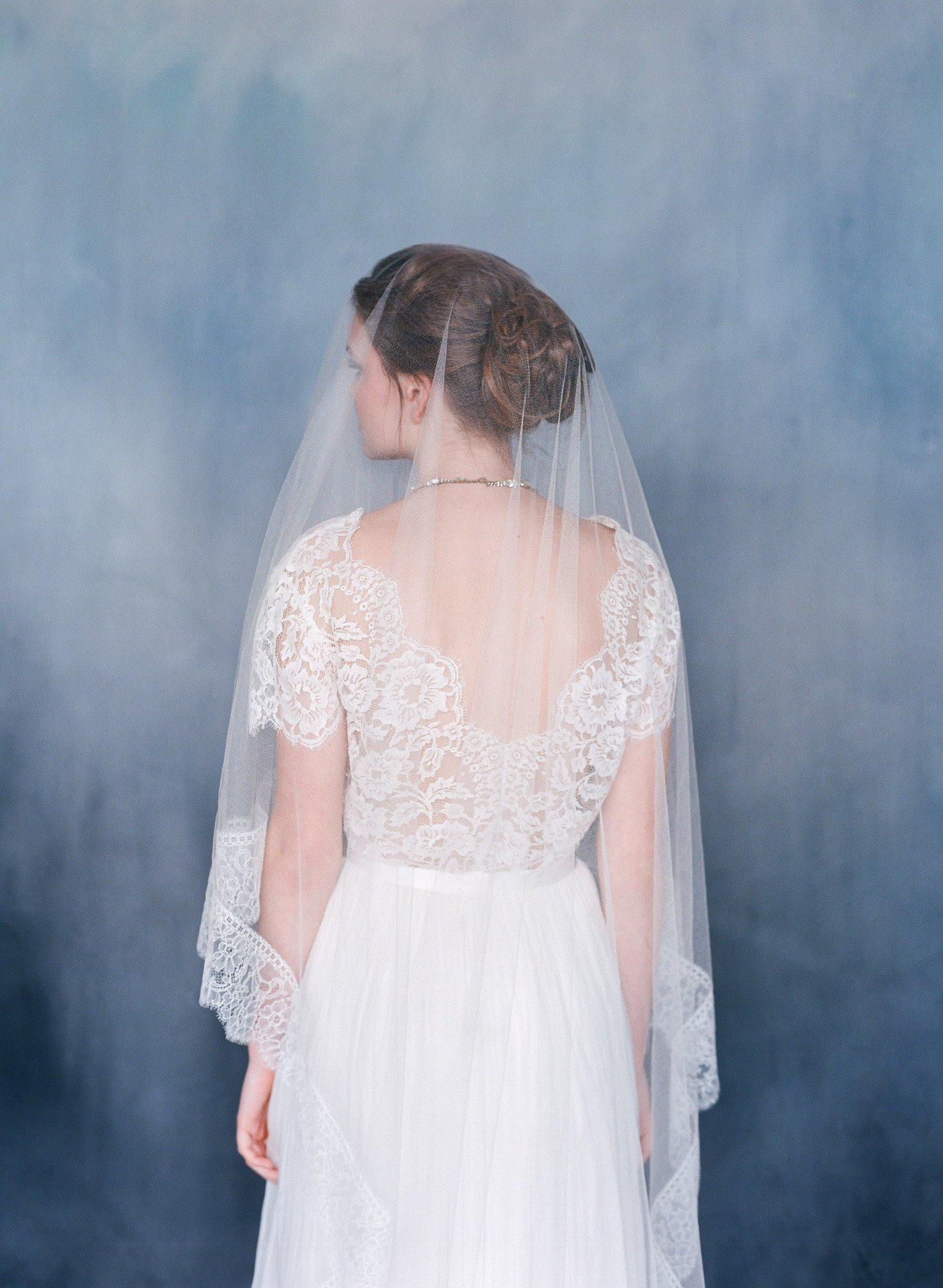 women showing the back of the sheer silk tulle veil and off white dress.